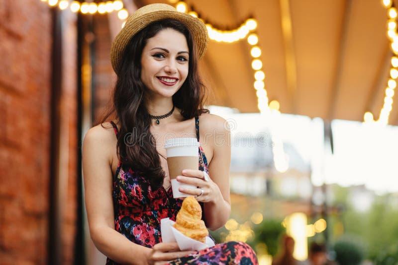 Mensen, voedsel, rust en levensstijlconcept Donkerbruine vrouw met lang haar, die de zomerkleding en hoed, het drinken meeneem ko stock afbeelding