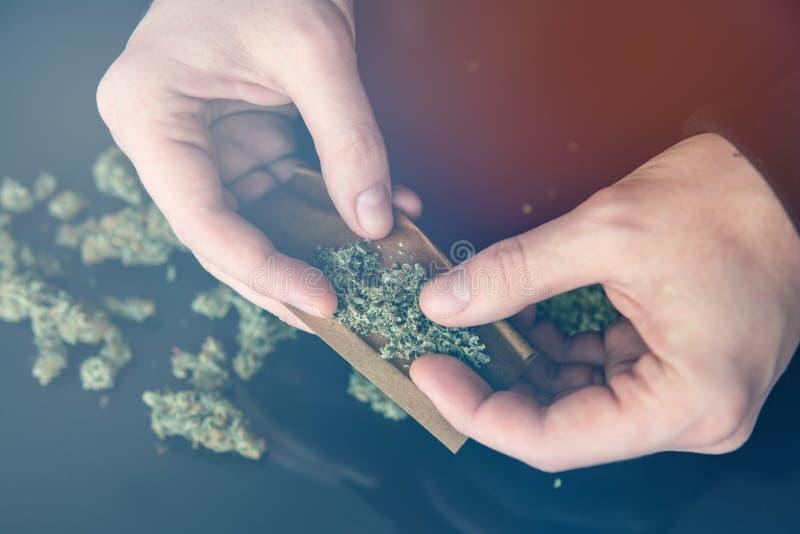 Mensen voorbereidingen treffende en rollende van de marihuanacannabis verbinding Sluit omhoog van verslaafdenverlichting op marih stock foto