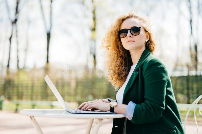 Mensen, vrije tijd, technologie en mededeling Mooie onderneemster die zonnebril en elegant jasje dragen die laptop computer met b royalty-vrije stock foto's