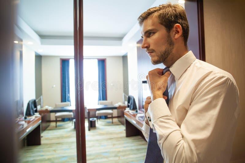 Mensen, zaken, manier en kledingsconcept - sluit omhoog van mens in overhemd en het aanpassen band die omhoog op hals zich thuis  stock afbeelding
