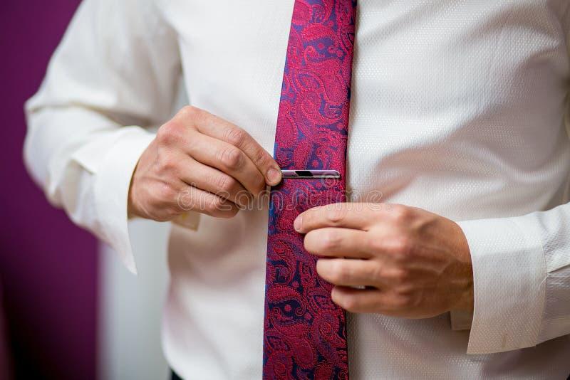 Mensen, zaken, manier en kledingsconcept - sluit omhoog van mens in overhemd zich en het aanpassen purpere band die omhoog met gr royalty-vrije stock afbeelding