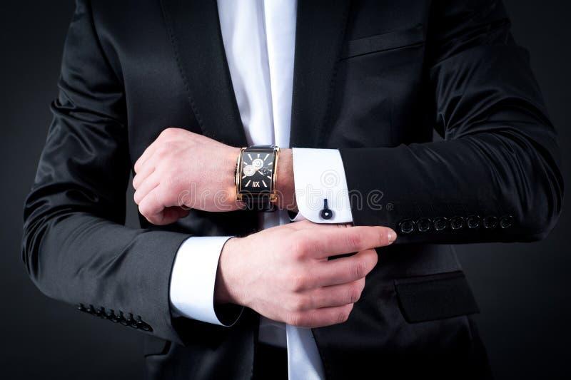 Mensen zwart kostuum en horloge stock afbeelding