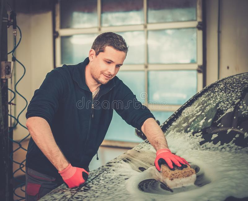 Mensenarbeider op een autowasserette stock foto