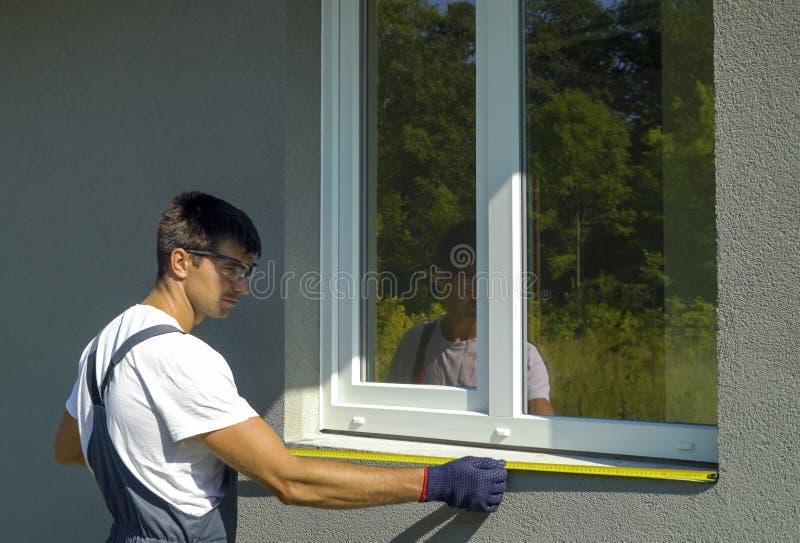 Mensenarbeider in veiligheidsbril die oppervlakte voor pvc-de vensterbankinstallatie van het venstermetaal schoonmaken stock afbeelding