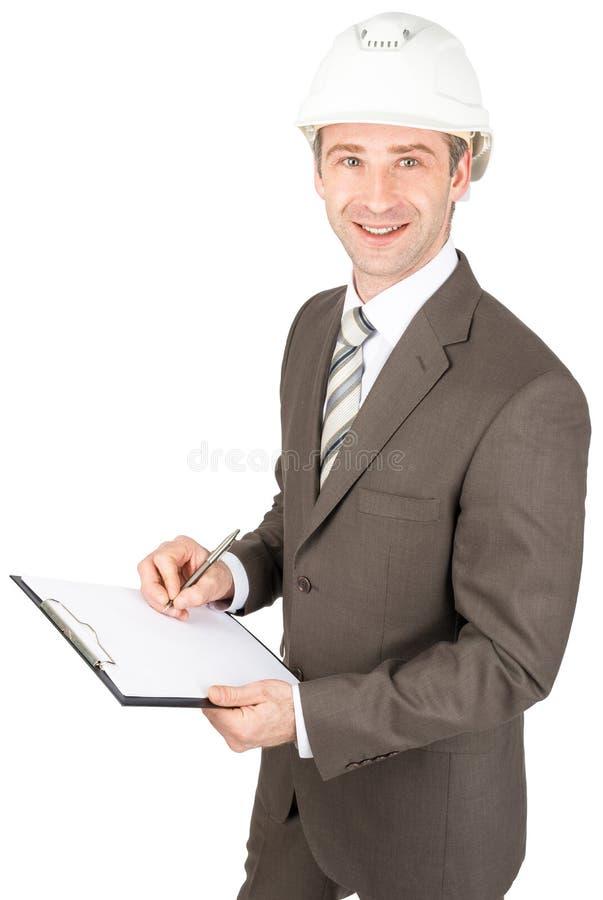 Mensenarchitect die in helm op document schrijven stock fotografie