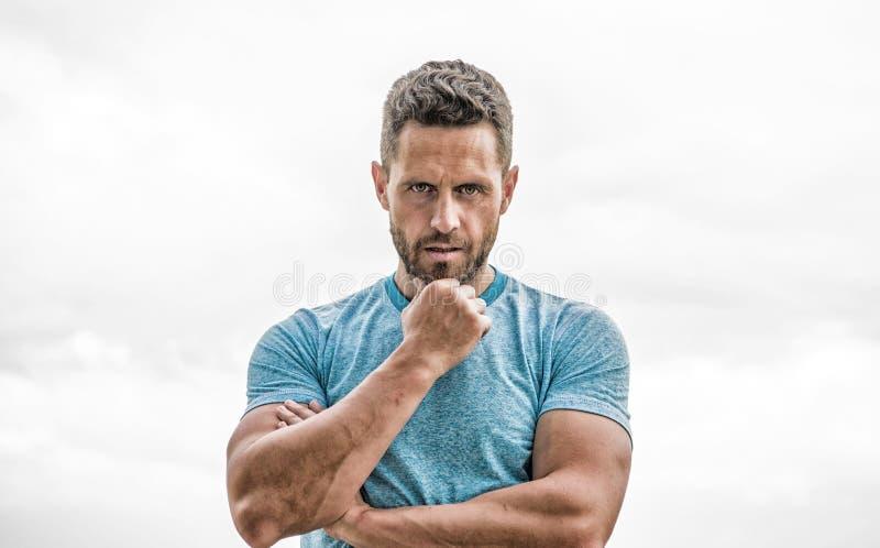 mensenatleet in blauwe sportt-shirt Sportkledingsmanier Spiermannetje met baard Nadenkende die mens op wit wordt ge?soleerd stock foto's