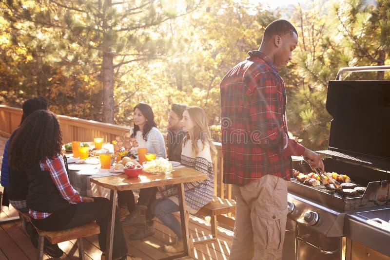 Mensenbarbecues voor vrienden bij een lijst aangaande een dek in een bos stock foto