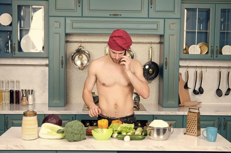 Mensenbespreking op mobiele telefoon in keuken Kok in chef-kokhoed met sexy torso bij lijst Vegetarisch menu en gezonde voeding V royalty-vrije stock fotografie