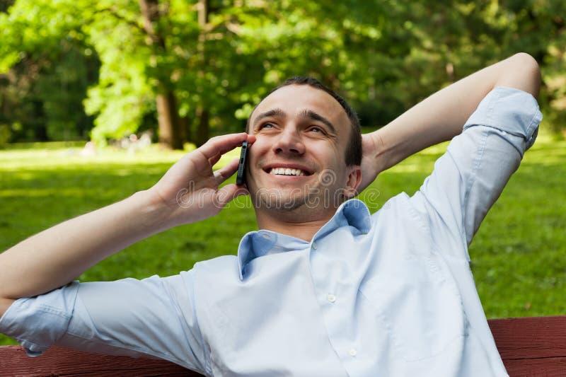 Mensenbespreking telefonisch in het park stock fotografie