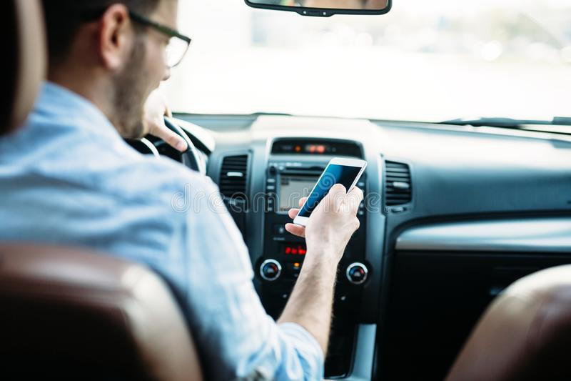 Mensenbestuurder die slimme telefoon op weg in auto met behulp van royalty-vrije stock foto