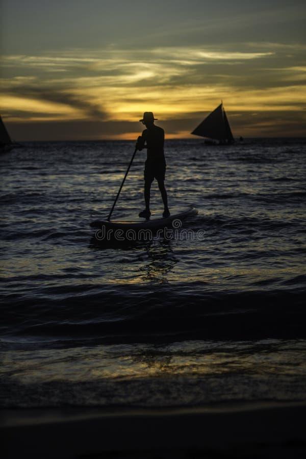 Mensenbrandingen op oceaan dichtbij strand bij zonsondergang royalty-vrije stock afbeeldingen