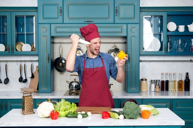 Mensenchef-kok met boos gezicht met de peper van de messenbesnoeiing royalty-vrije stock afbeelding