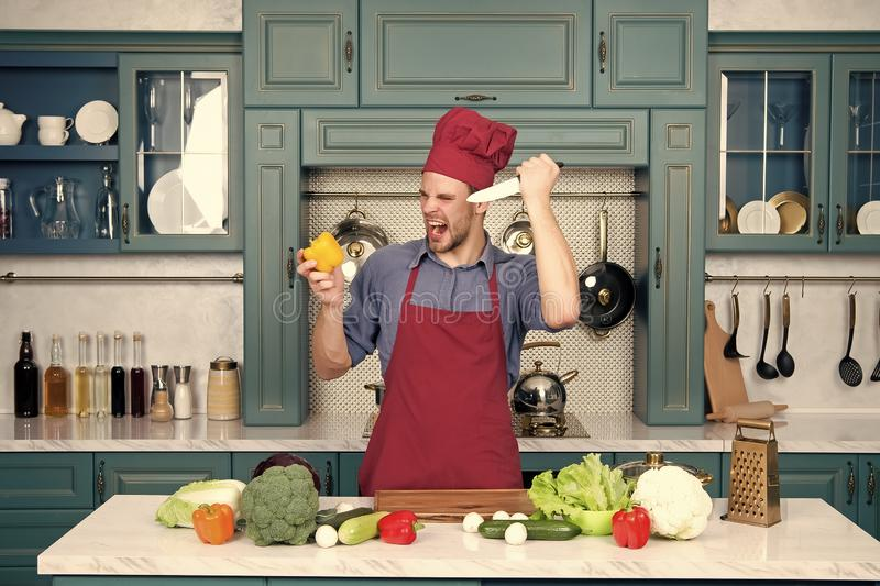 Mensenchef-kok met boos gezicht met de peper van de messenbesnoeiing royalty-vrije stock foto's