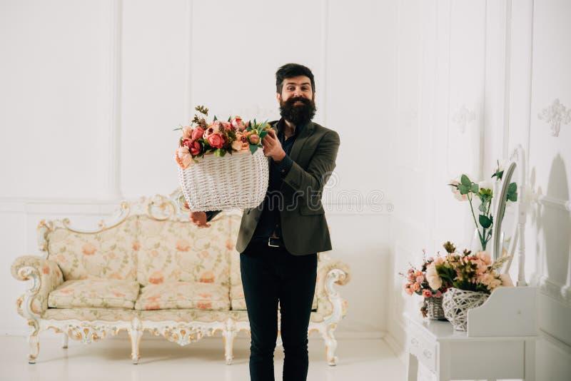 Mensenconcept Mens met de mand van de baardgreep met rozen Mensenbloemist met bloemdecor Mens geworden bloemen voor vakantie royalty-vrije stock foto's