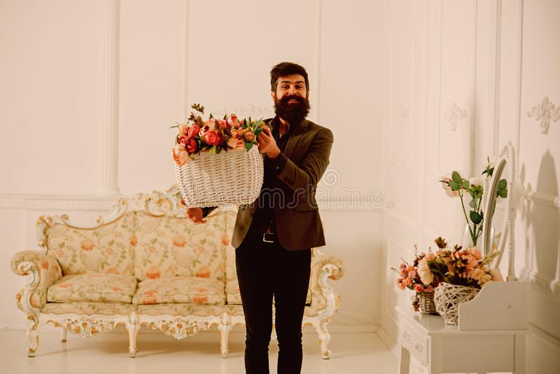 Mensenconcept Mens met de mand van de baardgreep met rozen Mensenbloemist met bloemdecor Mens geworden bloemen voor vakantie royalty-vrije stock afbeelding