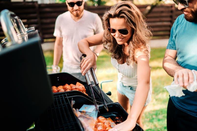 Mensenconcept - Vrienden die een barbecuepartij in aard hebben terwijl het hebben van een het goede tijd, drinken, koken en eten royalty-vrije stock afbeelding
