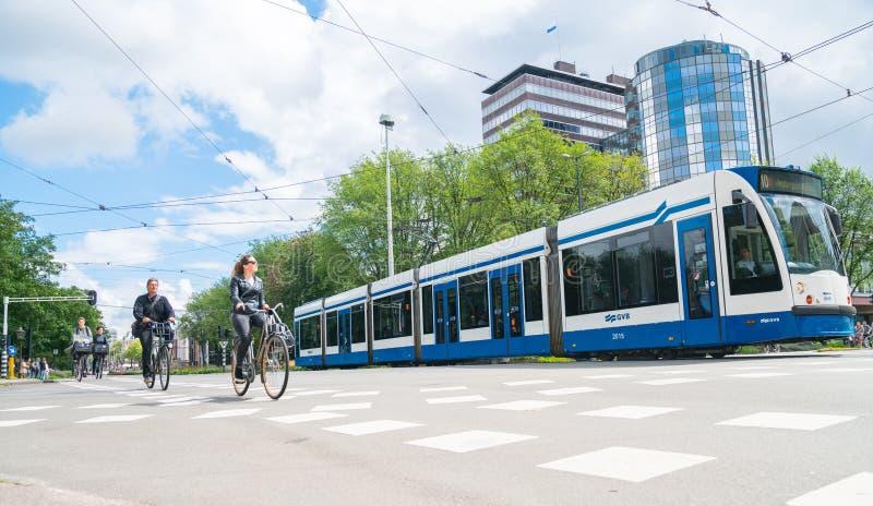Mensencyclus met tram door stadskruising met moderne bureaugebouwen op achtergrond stock afbeeldingen
