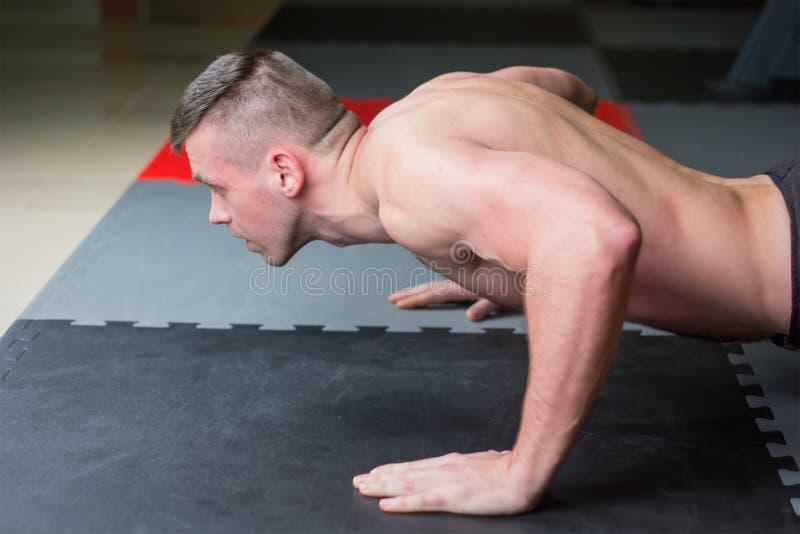 Mensenduw op borstoefening en zanderige ernstige gelaatsuitdrukking binnen gymnastiek royalty-vrije stock afbeeldingen