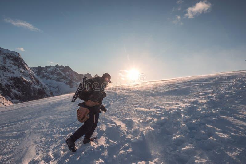 Mensenfotograaf die op sneeuwberg met blauwe hemel bij zonsondergang beklimmen royalty-vrije stock afbeelding