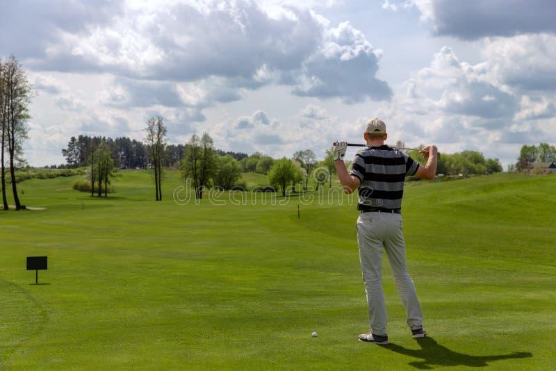 Mensengolfspeler het stellen bij fairway op golfcursus stock afbeelding