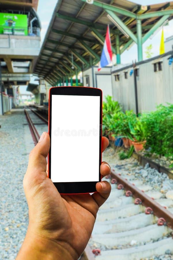Mensenhand die de telefoon en het witte scherm met onduidelijk beeldachtergrond houden stock fotografie