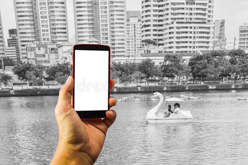 Mensenhand die de telefoon en het witte scherm met onduidelijk beeldzwarte houden & wh royalty-vrije stock foto's