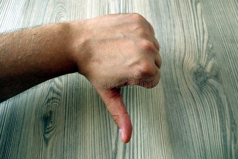 Mensenhand die duim onderaan gebaar, bedrijfsmislukkingsverwerping en afkeuringsconcept tonen stock fotografie