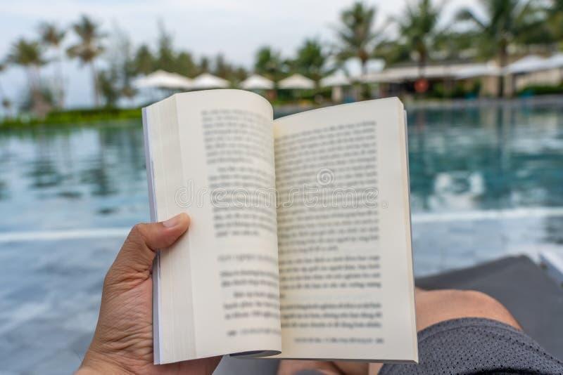 Mensenhand die een boek met zwembadachtergrond houden royalty-vrije stock afbeeldingen