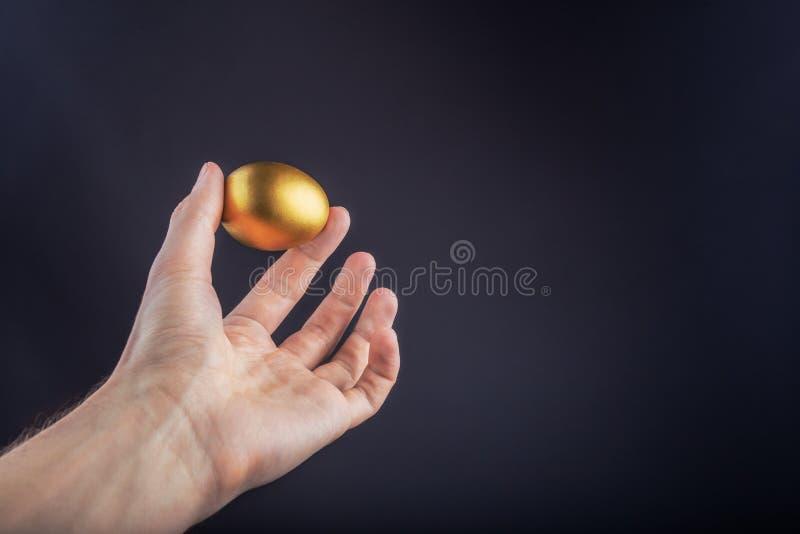 Mensenhand die Gouden ei op een zwarte achtergrond houdt royalty-vrije stock foto's