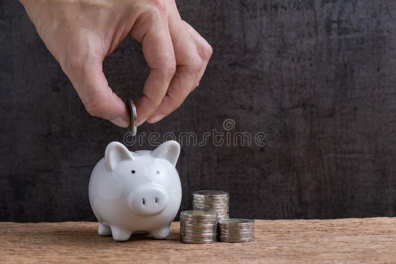 Mensenhand die muntstuk zetten in spaarvarken met stapel muntstukkentorens royalty-vrije stock afbeelding