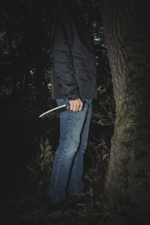 Mensenhand met mes in het hout royalty-vrije stock fotografie