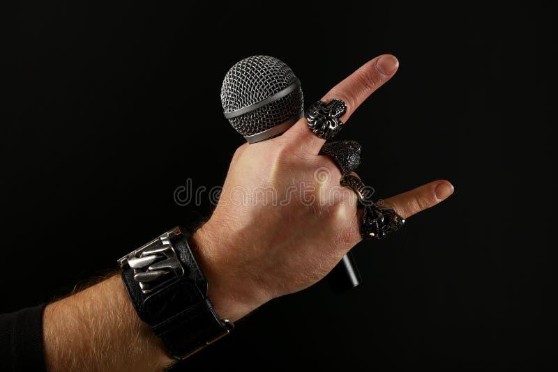 Mensenhand met microfoon op zwarte wordt geïsoleerd die stock afbeelding