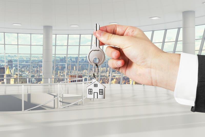 Mensenhand met sleutels met licht leeg bureau op achtergrond royalty-vrije stock afbeelding