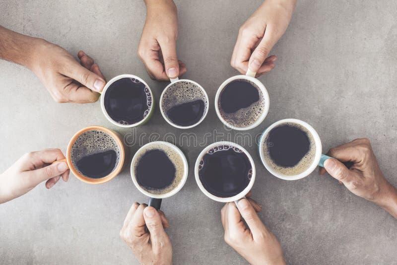 Mensenhanden die koppen van koffie houden stock afbeeldingen