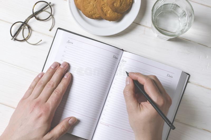 Mensenhanden die nota's schrijven aan het notitieboekje op houten lijst in huisbureau stock foto