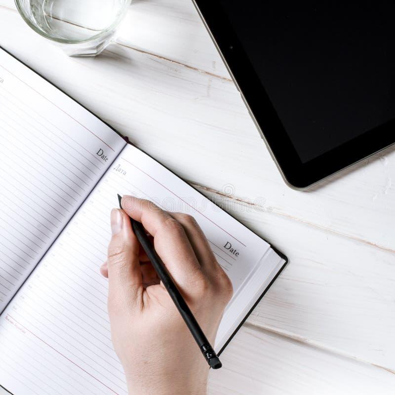 Mensenhanden die nota's schrijven aan het notitieboekje op houten lijst in huisbureau stock afbeeldingen