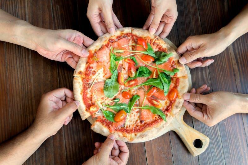 Mensenhanden die Plakken van Salmon Pizza met raket en tomaat nemen Hoge de groepshanden die van de hoekvriend een plak van pizza stock afbeeldingen