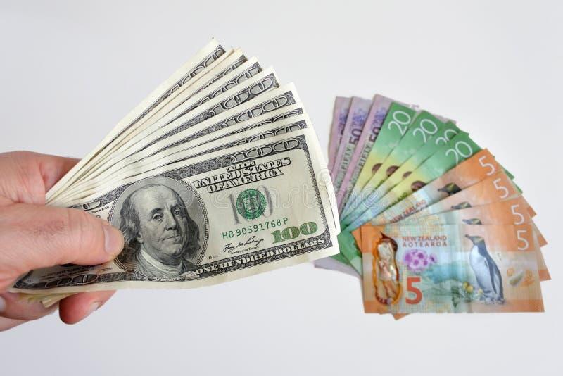Mensenhanden die stevig vele honderd van de nota's van de Amerikaanse dollarmunt houden tegen de muntrekeningen van Nieuw Zeeland royalty-vrije stock fotografie