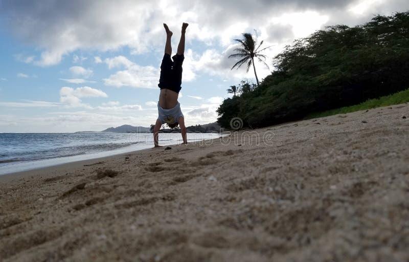 Mensenhandstand op strand als golfbroodje op kust stock afbeeldingen