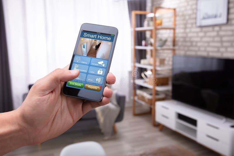 Mensenholding Cellphone met Smart Hometoepassing royalty-vrije stock fotografie