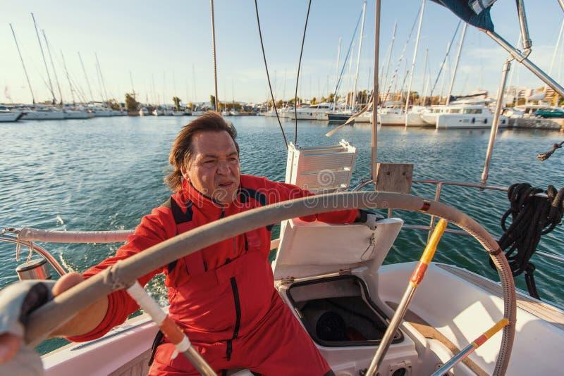 Mensenkapitein bij de roercontroles van een varend jacht Sport stock afbeelding