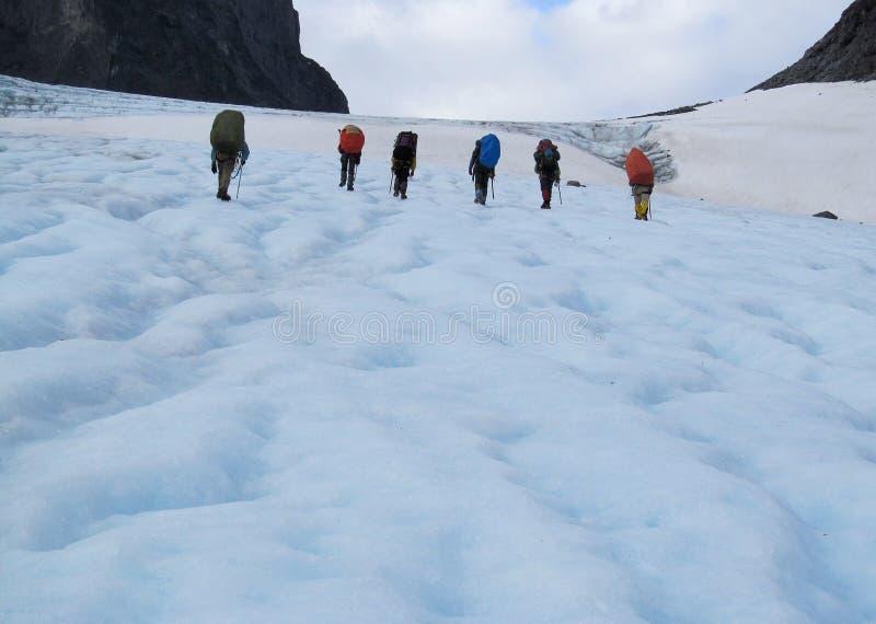Mensenklimmers, die sneeuwtop, rotsachtige bergpieken en gletsjer in Noorwegen beklimmen stock foto's