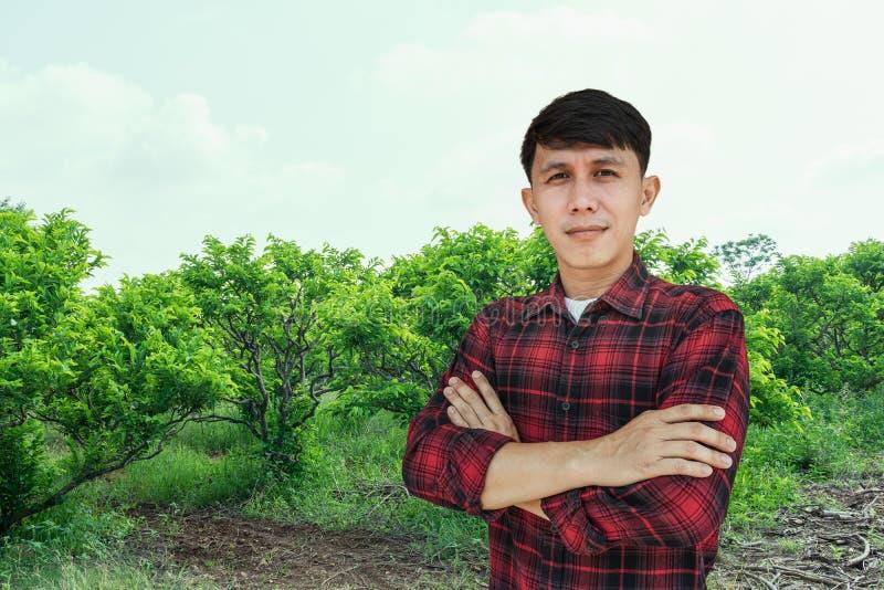 Mensenlandbouwer die en zich op de achtergrond van de de bomenboomgaard van de vlaappel glimlachen bevinden stock afbeelding
