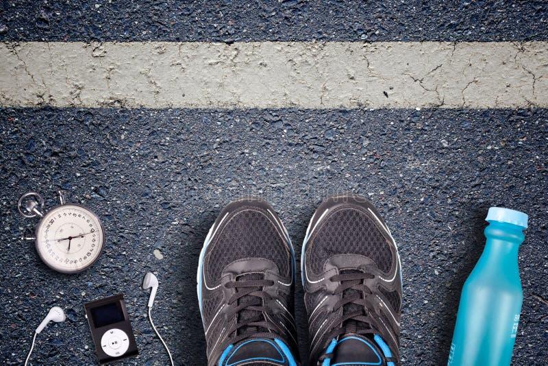 Mensenloopschoenen en looppasmateriaal op asfalt Lopende opleiding op harde oppervlakten De chronometer van het agentmateriaal en stock afbeelding