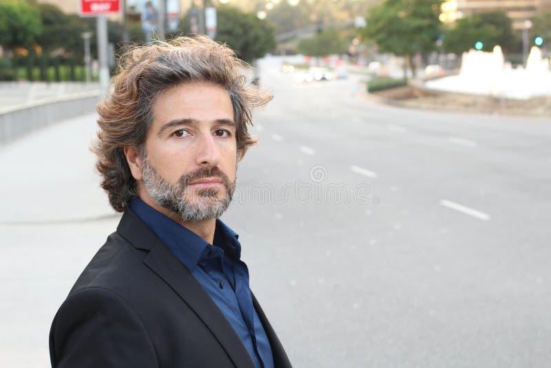 MENSENmacht Zich kleedt in donker kostuum bevindt een knappe, sexy, middenleeftijdszakenman zich buiten in de stadsstraten royalty-vrije stock foto