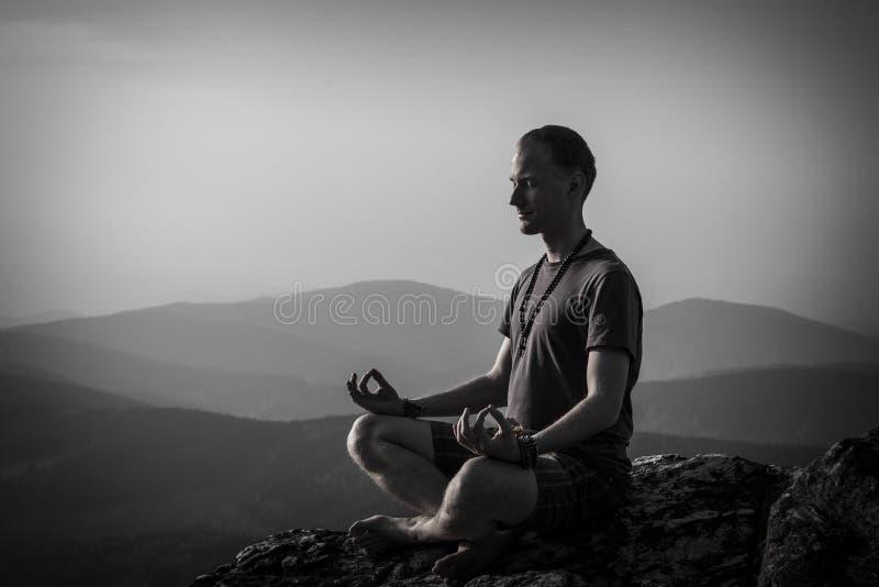 Mensenmeditatie op een rots stock afbeeldingen