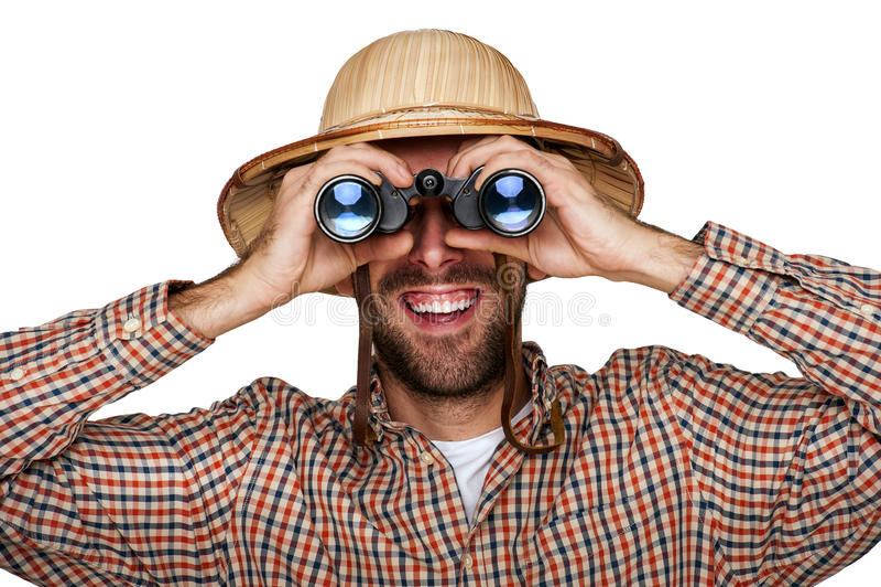 Mensenontdekkingsreiziger die in wandelaaroverhemd door verrekijkers met reizigershoed kijken stock fotografie