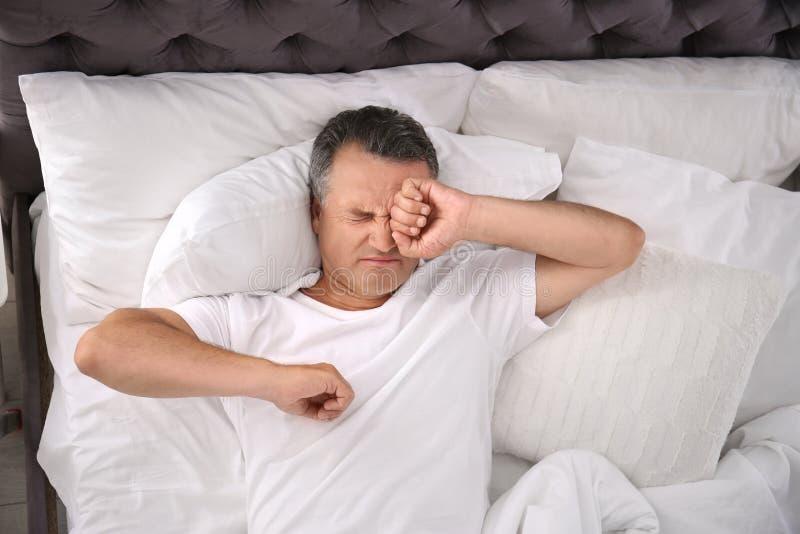 Mensenontwaken na het slapen op comfortabel hoofdkussen stock fotografie