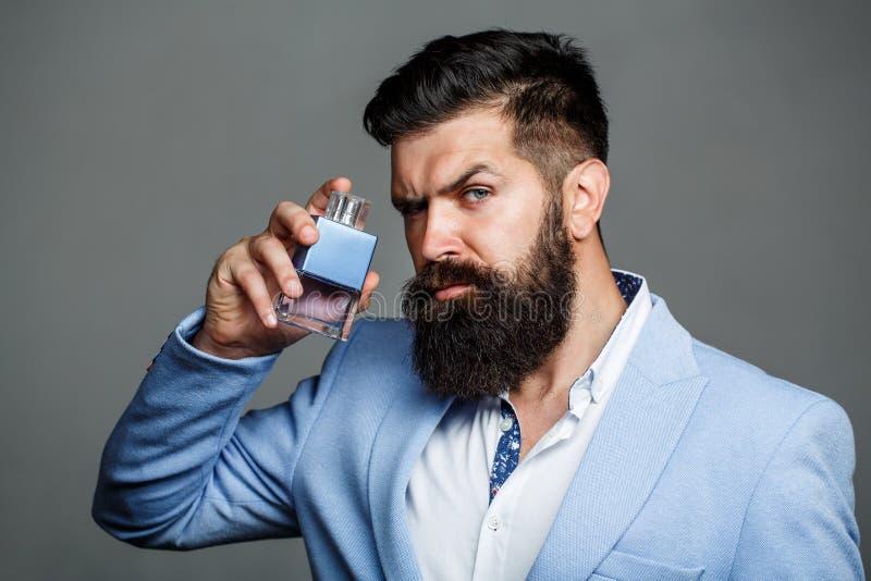 Mensenparfum, geur Mannelijk parfum Mannelijke geur en parfumerie, schoonheidsmiddelen Gebaarde mens die fles steunen van stock afbeeldingen