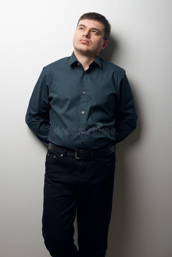 Mensenportret gekleed in donker overhemd en zwarte broek over grijze achtergrond stock afbeeldingen